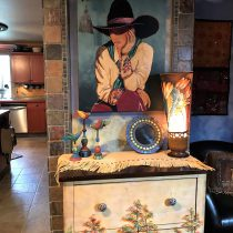 Cowgirl artwork, beautiful fringed leather on a decorated chest.